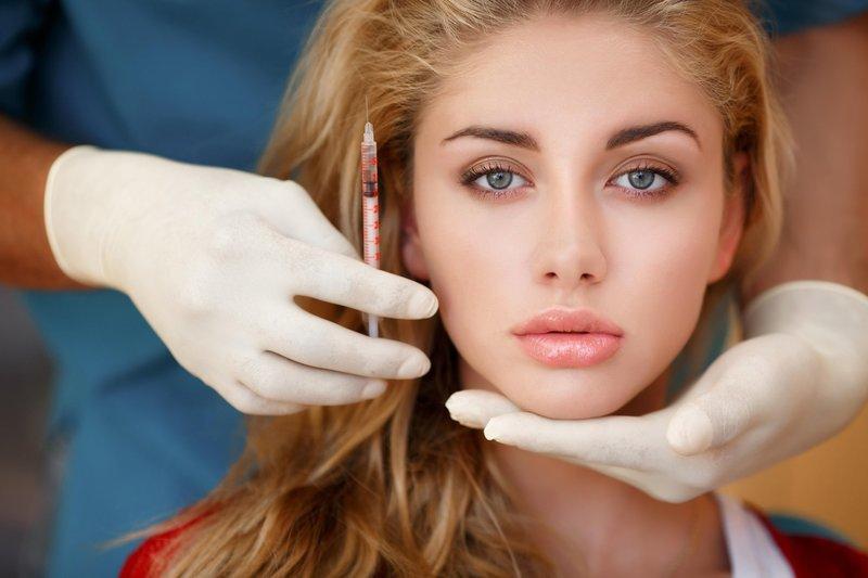 Девушка на приеме у косметолога для коррекции перманентного макияжа губ