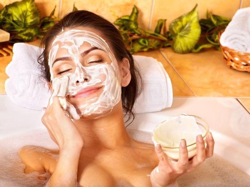 Девушка наносит на лицо очищающую маску