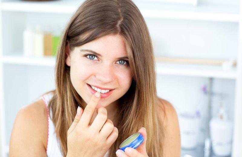 Девушка смазывает губы вазелином