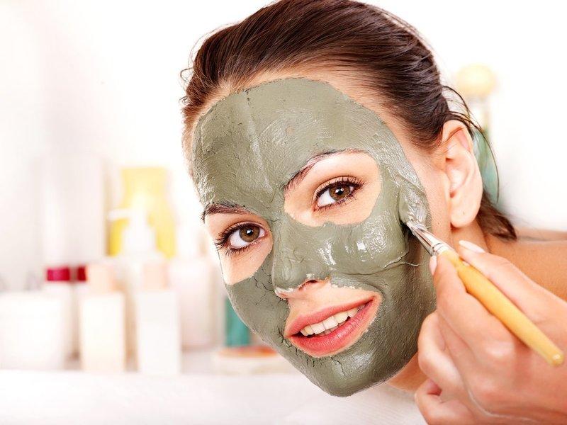Девушка наносит на лицо очищающую маску из глины