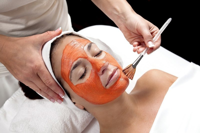 Девушке наносят кистью на кожу лица маску из моркови