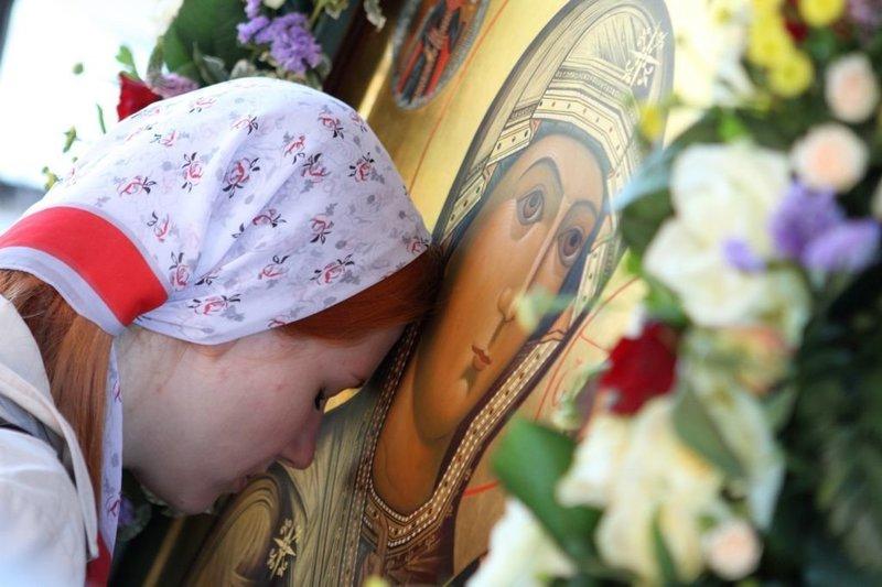 Девушка кланяется иконе Богоматери