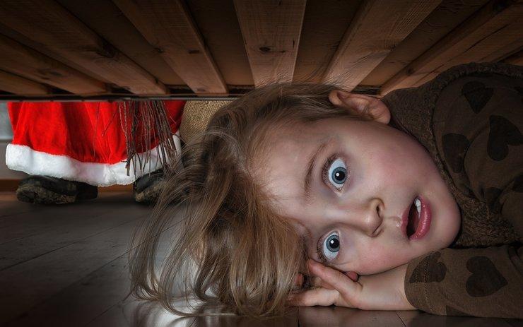 Испуганный ребёнок прячется под кроватью