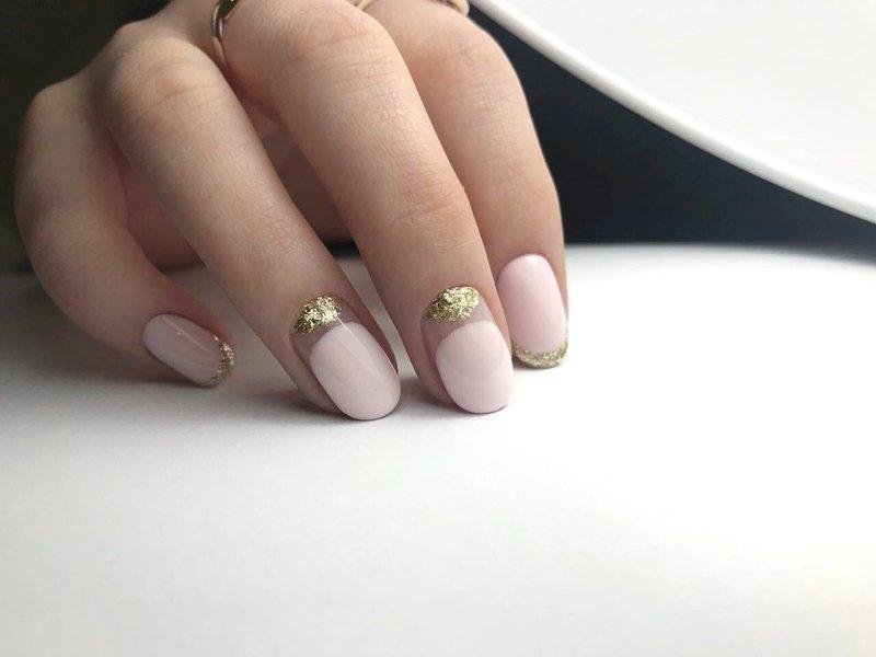Маникюр в стиле нюд с золотыми лунками и френчем