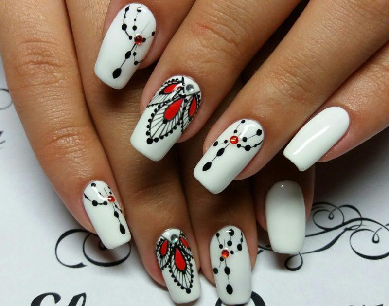 Белые ногти с чёрно-красными узорами