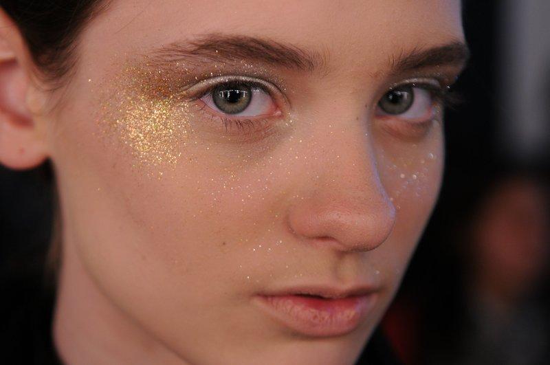 Нюдовый макияж с золотым глиттером на лице