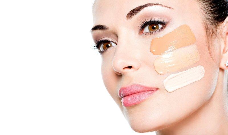 Девушка с палитрой различных по цвету тональных кремов на лице