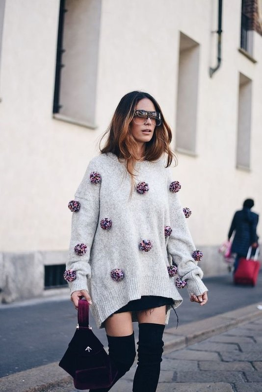 Девушка в свитере оверсайз с помпонами