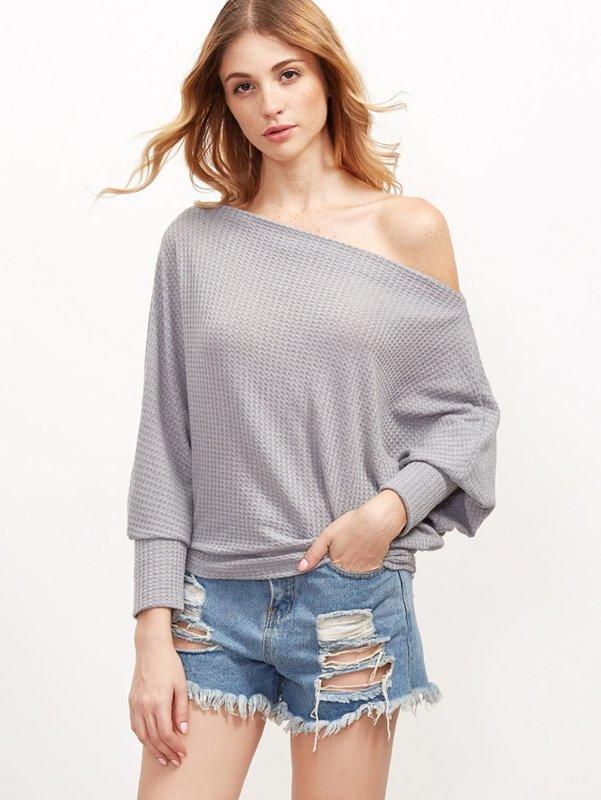 Девушка в свитере с открытыми плечами и коротких шортах