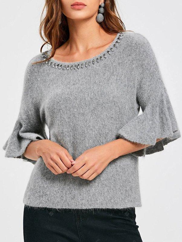 Девушка в свитере с рукавами-колоколами