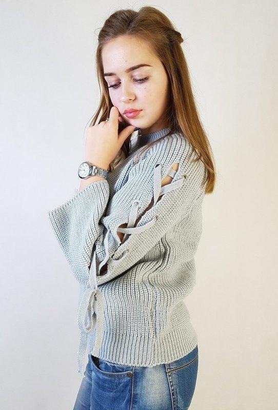 Девушка в свитере с завязками вдоль рукавов