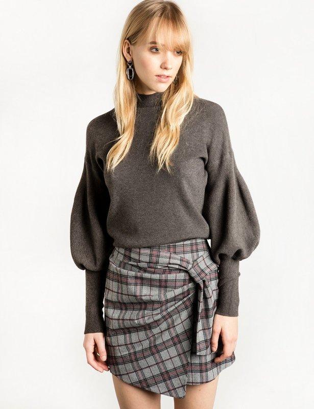Девушка в свитере с рукавами буф