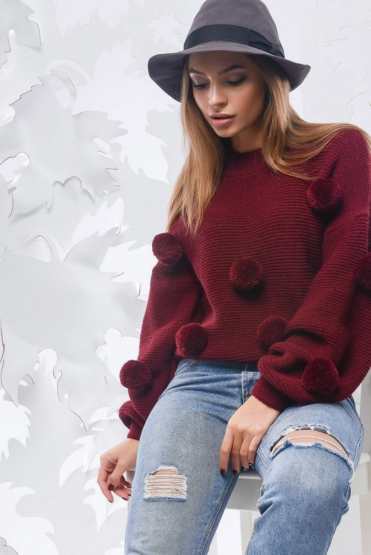 Девушка в свитере с однотонными помпонами