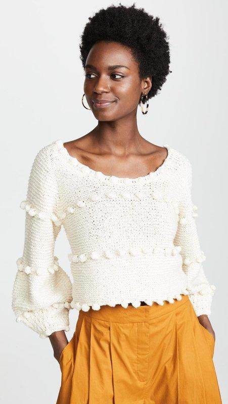 Девушка в свитере с помпонами и юбке