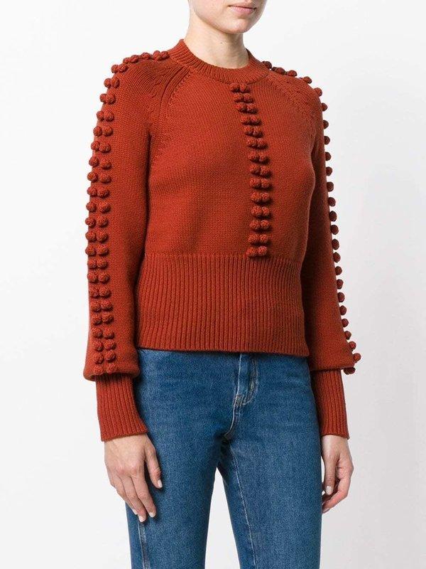 Девушка в свитере с фактурными помпонами