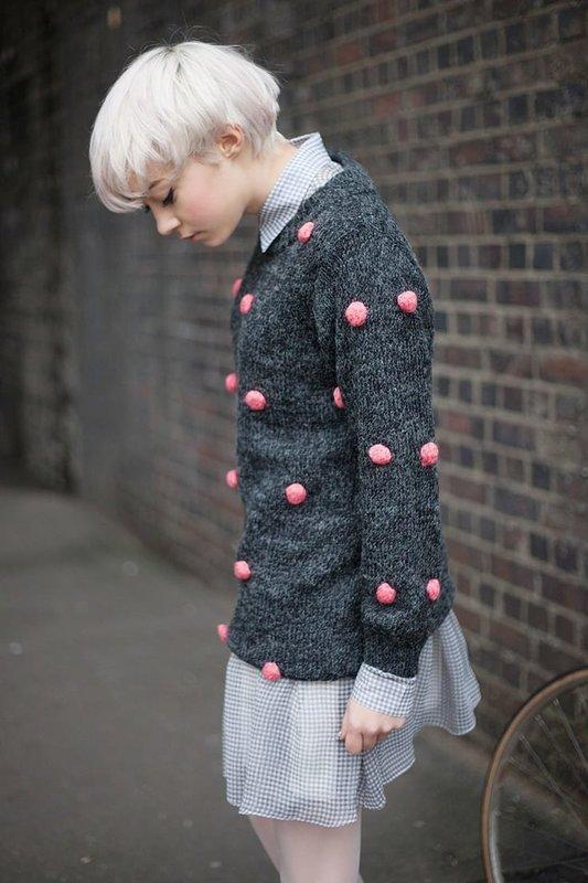 Девушка в свитере с розовыми помпонами поверх платья