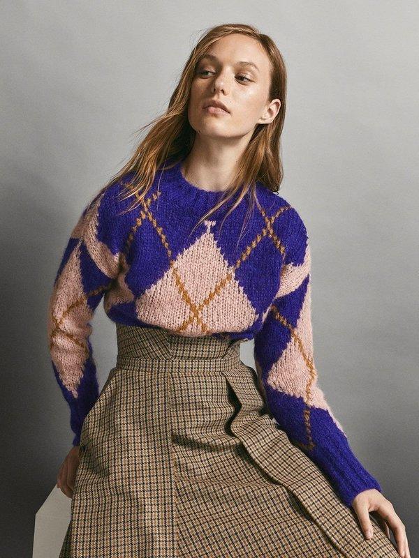 Девушка в свитере с ромбовидным принтом и юбке