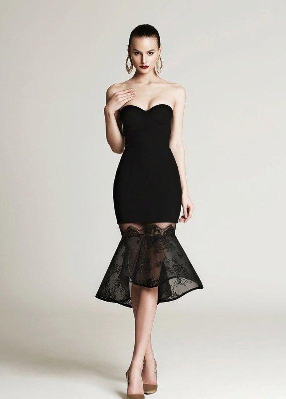 Девушка в черном коктейльном платье с открытыми плечами