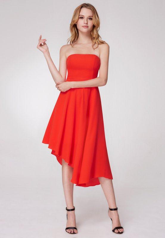 Девушка в оранжевом коктейльном платье с открытыми плечами и асимметричным подолом