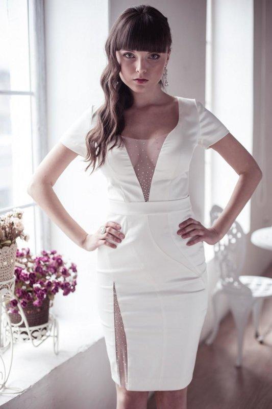 Девушка в белом коктейльном платье с глубоким декольте