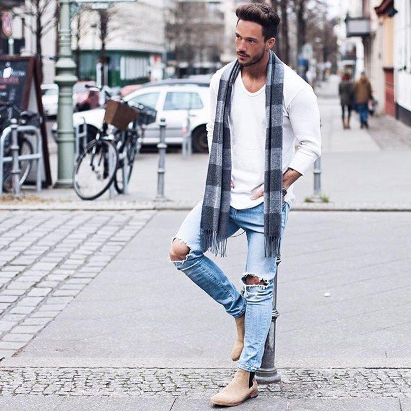 Мужчина в рваных джинсах и белом свитере