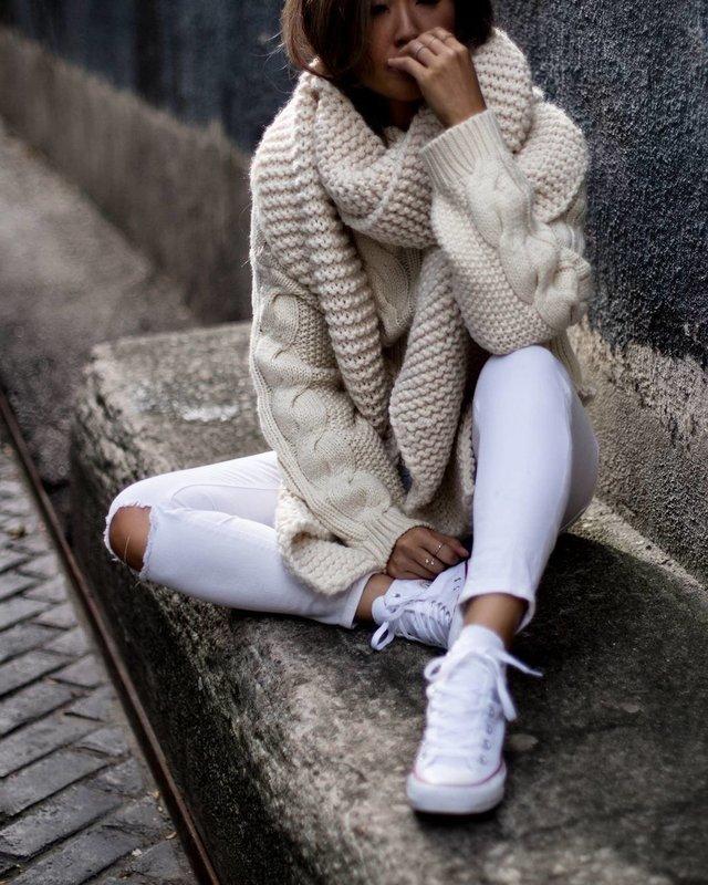Девушка в свитере крупной вязки и широким воротом