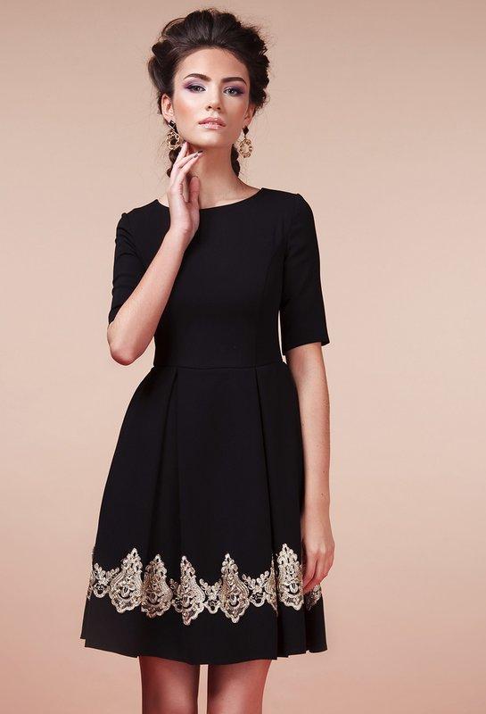 Девушка в черном коктейльном платье А-силуэта с кружевной вставкой