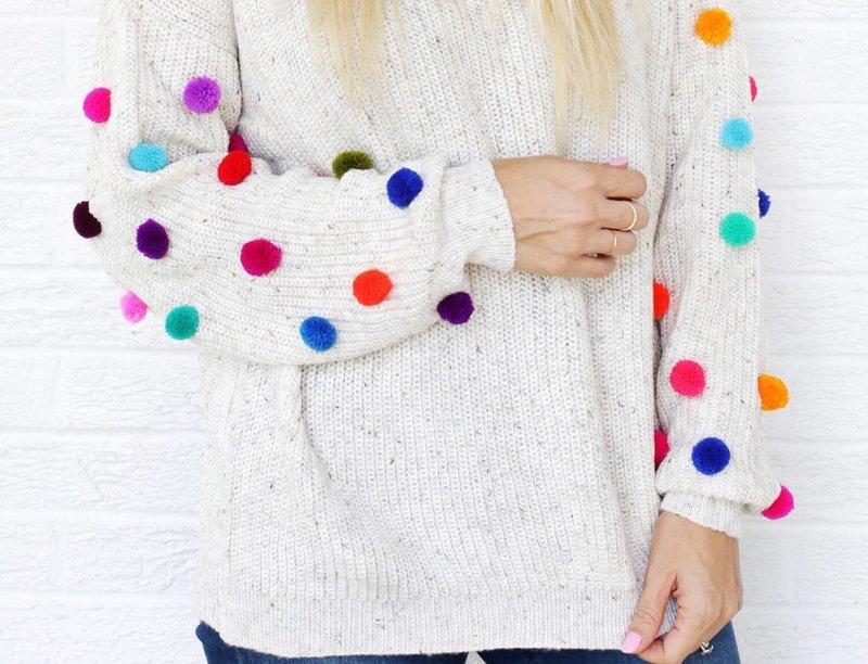 Девушка в свитере с помпонами