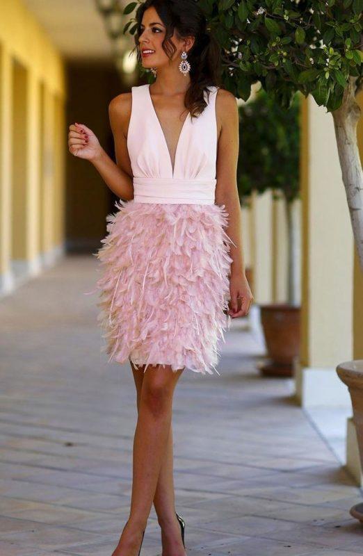 Девушка в коктейльном платье с перьями на юбке