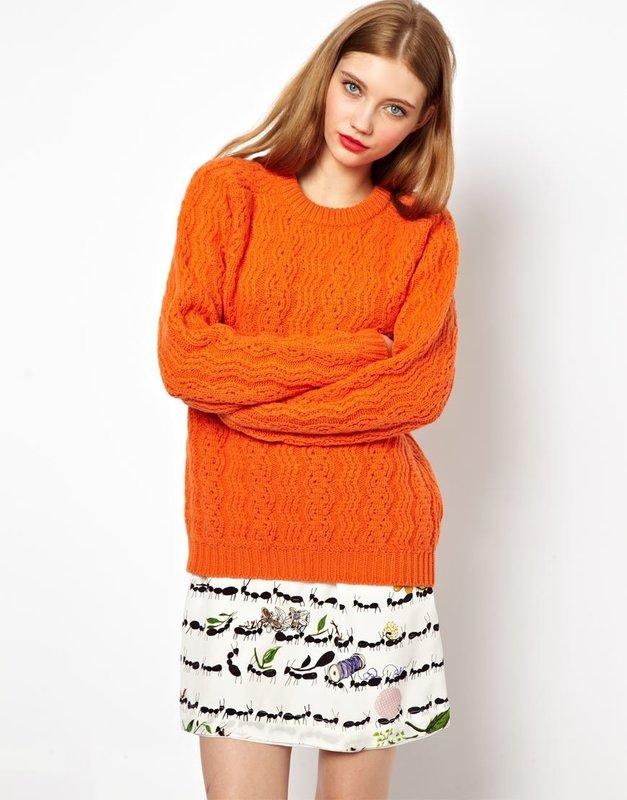 Девушка в оранжевом свитере и юбке