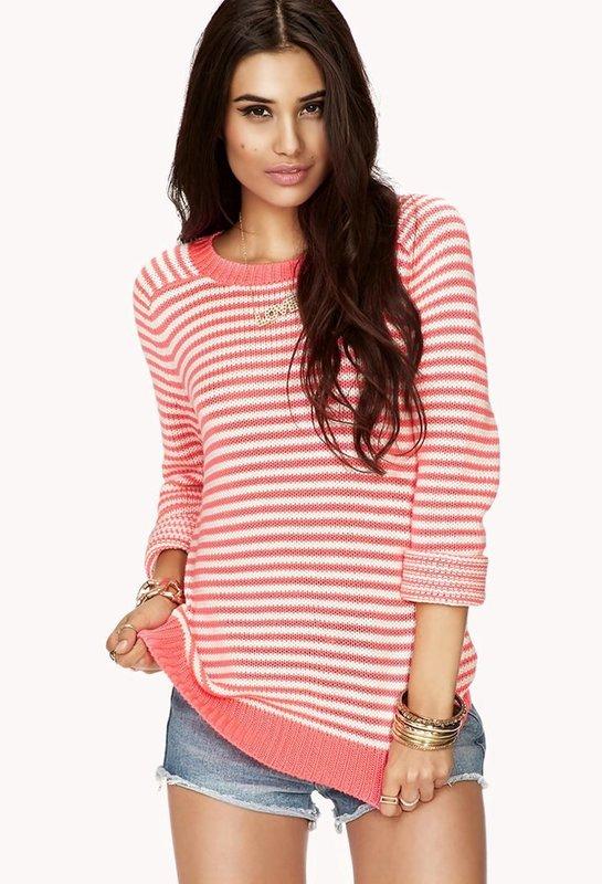 Девушка в свитере в горизонтальную полоску и шортах