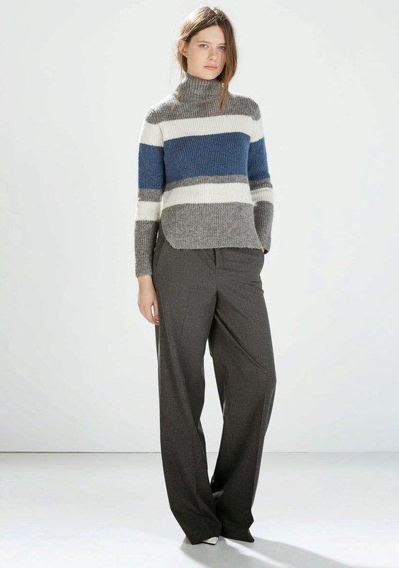 Девушка в свитере в горизонтальную полоску и брюках