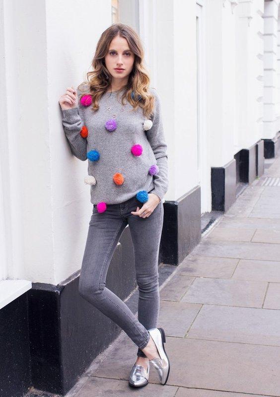 Девушка в свитере с разноцветными помпонами