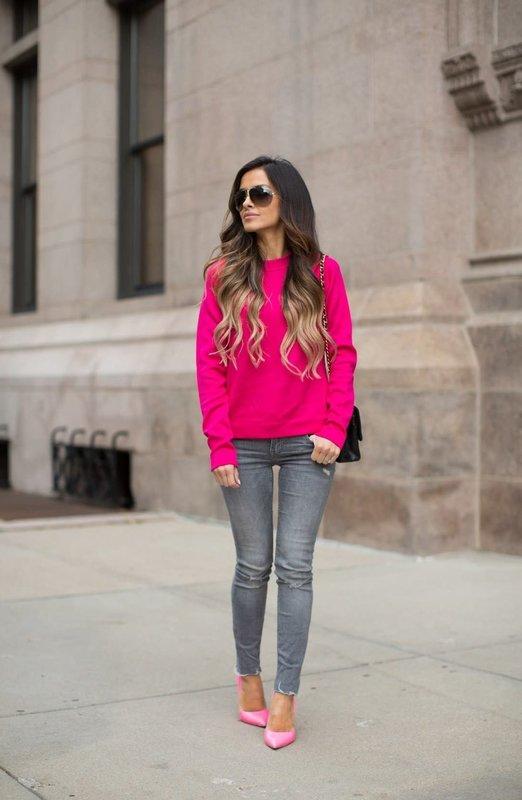 Девушка в ярком розовом свитере и джинсах-скинни