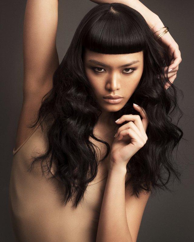 Девушка с короткой, густой челкой в сочетании с длинными вьющимися волосами