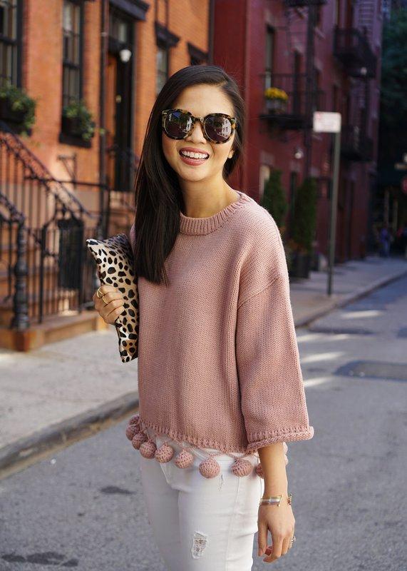 Девушка в свитере с помпонами на подоле