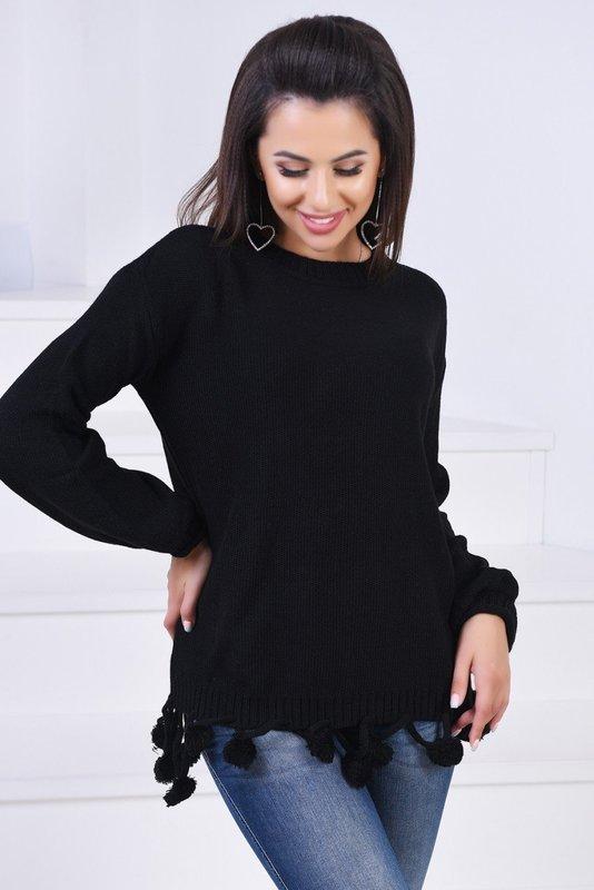 Девушка в черном свитере с помпонами на подоле