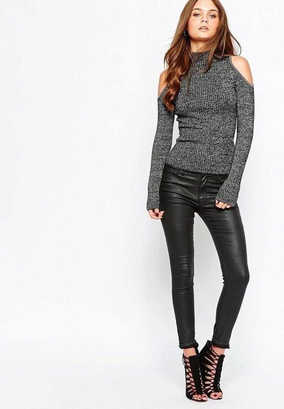 Девушка в свитере с вырезами на плечах и кожаных леггинсах