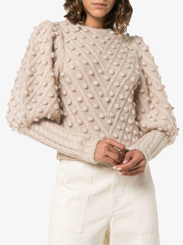 Девушка в бежевом свитере с помпонами