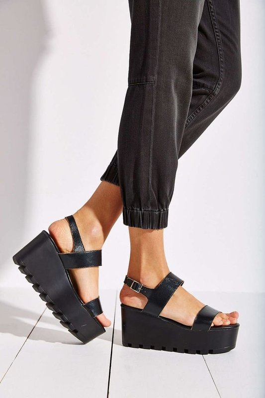 Девушка в сандалях на высокой сплошной платформе