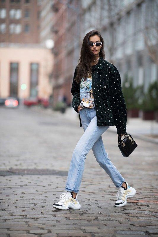 Девушка в громоздких кроссовках в сочетании с джинсами