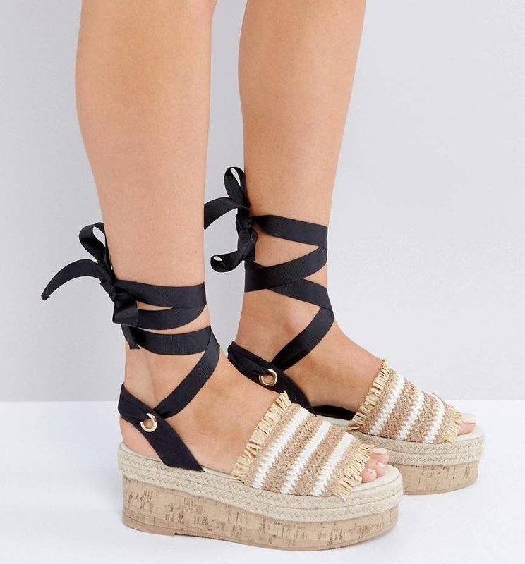 Девушка в сандалиях на платформе с атласными лентами