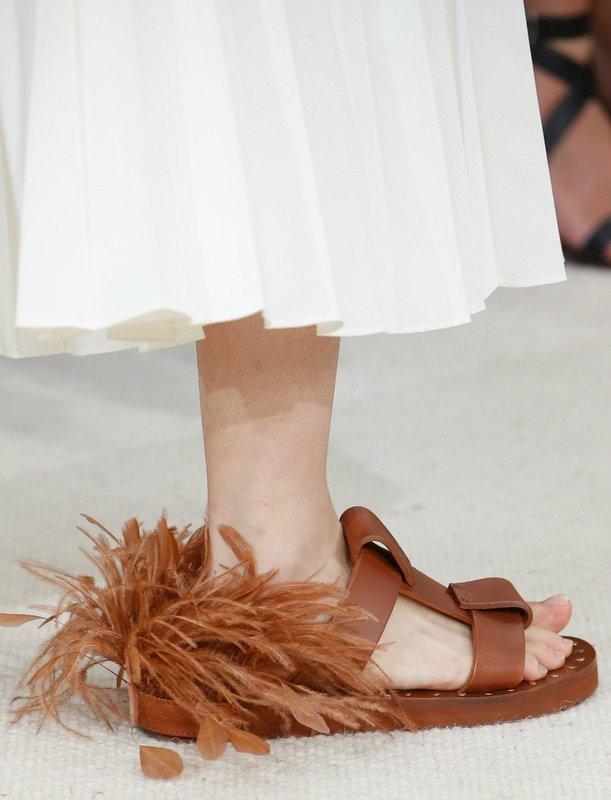 Девушка в сандалях с перьями сзади