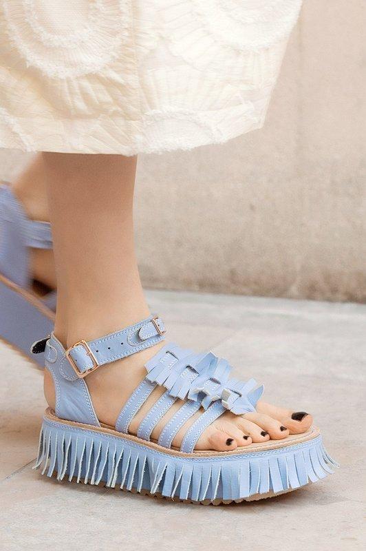 Девушка в сандалях с бахромой по краю подошвы