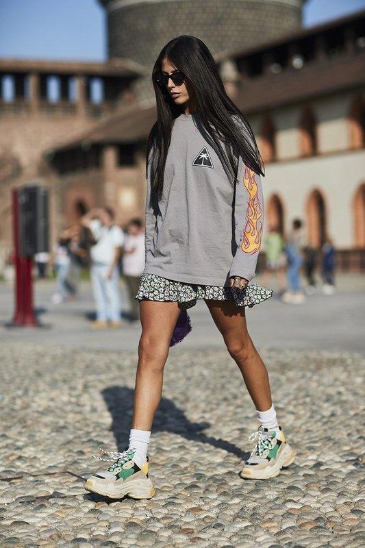 Девушка в громоздких кроссовках в сочетании с юбкой