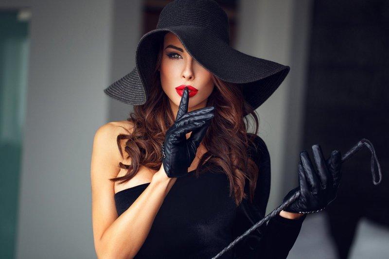 Девушка в перчатках с плеткой