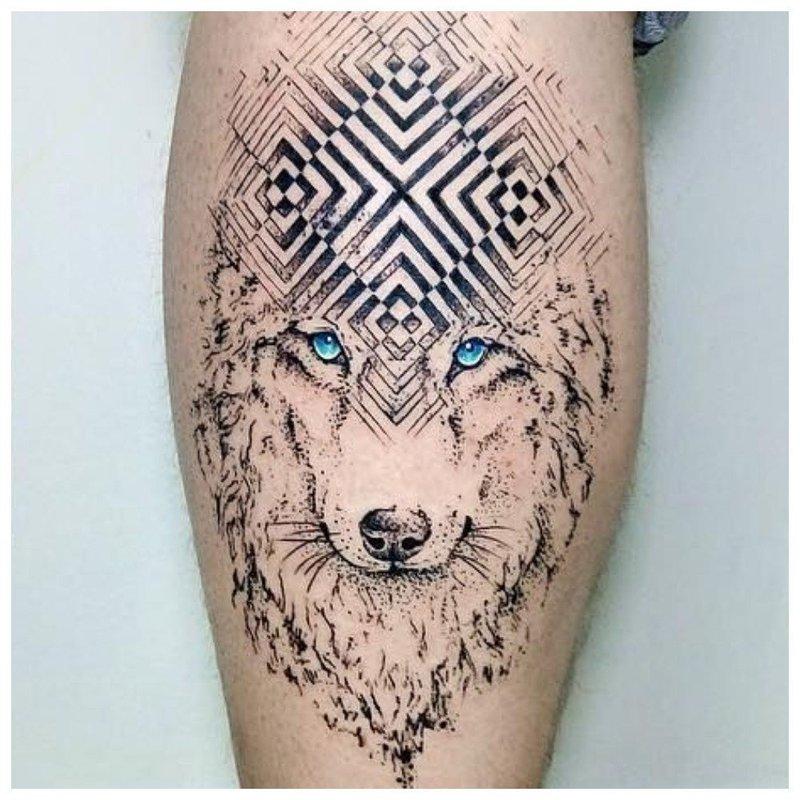 Символическое тату волка у мужчины на икре