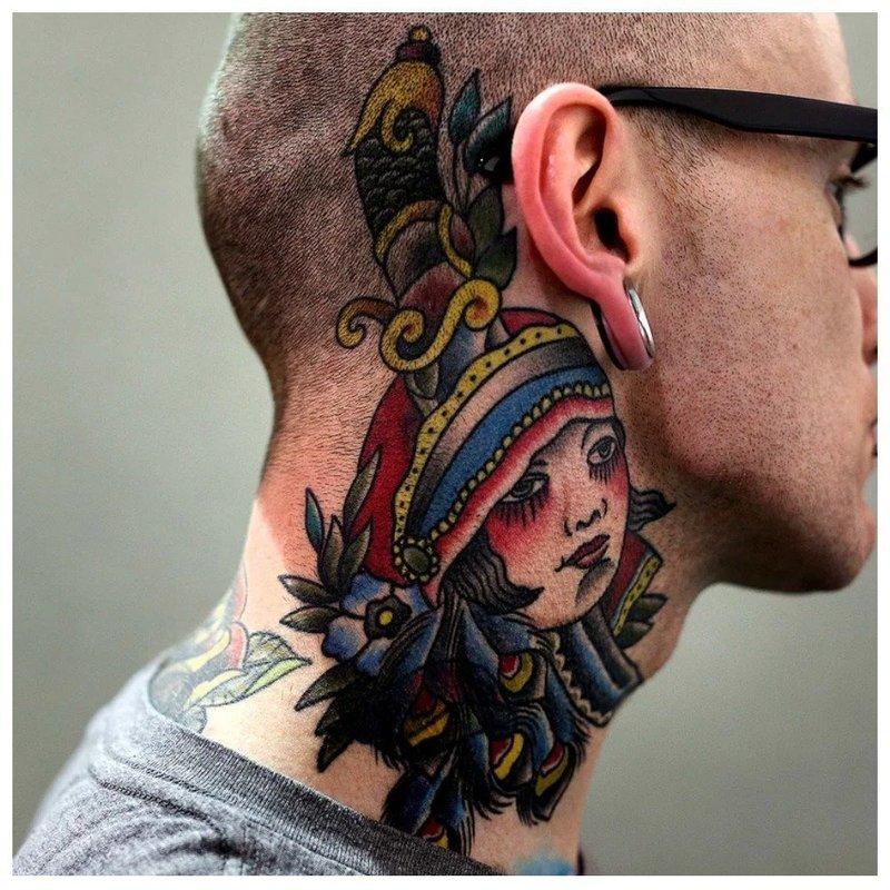Яркая татуировка на шее за ухом