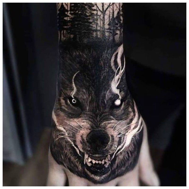 Тату волчьей пасти у мужчины на руке