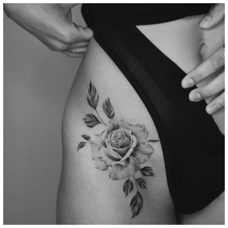 Нежный цветок на бедре сбоку у девушки